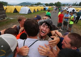 Nate Feldman, 17, from Old Bridge, New Jersey, is all smiles as he is stuck in a group hug at Base Camp Foxtrot on the last day of the 2013 National Scout Jamboree on Sunday, July 21, 2013.