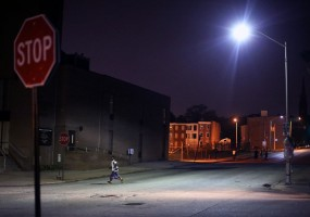 An 11-year-old boy crosses the street in East Baltimore two minutes before the 9pm Baltimore City curfew for youth. Youth caught outside after hours could face fines and be may be detained until a guardian picked them up.