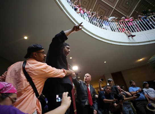 Rev. William Barber jumps up on the ledge around the pool to tell observers not to boo the local authorities efforts to keep the crowd safe during the Moral Monday protests at the North Carolina Legislative Building in downtown Raleigh on Monday, July 8, 2013.