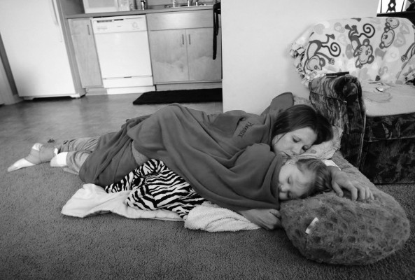 "Shelly Shrum sleeps with her daughter, Phoenix, 2, on the living room floor after watching ""Barney & Friends"" in their home on the Cedar Street property of the Daniel Pitino Shelter that works with homeless women and families."