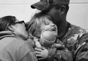 Phoenix laughs with her baby doll as she is hugged and kissed by her parents, Shelly and Stephen, before he heads to work early Friday morning.