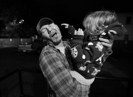 Stephen Shrum makes a face as he is slapped by his daughter, Phoenix, just after waking up Thursday morning to go to work. When he goes to work, Phoenix spends the remaining two hours of her mother's shift at the Daniel Pitino Shelter with her.
