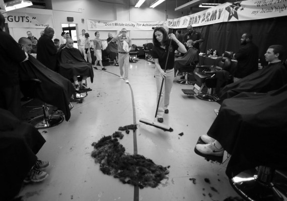 Administrative assistant Amanda Guinn sweeps up hair shaved off of almost 1,200 prospective plebes during Induction Day at the U.S. Naval Academy, Tuesday, July 1, 2014, in Annapolis, Md.