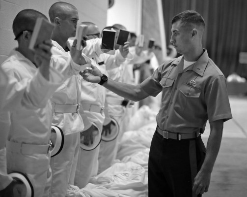 Plebes have the angle of their arms adjusted as they study their reef points, which contain basic information on how to act as a midshipmen during Induction Day.