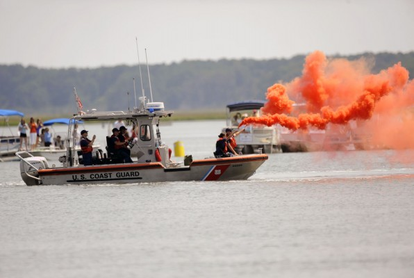 "A US Coast Guard boat sends off red smoke to signal the start of the 89th annual Pony Swim to the Island of Chincoteague, Va., on Wednesday, July 30, 2014. About 150 wild ponies hit the water at Assateague Island and swam across the channel in an annual tradition made famous by Marguerite Henry's 1947 novel ""Misty of Chincoteague."""