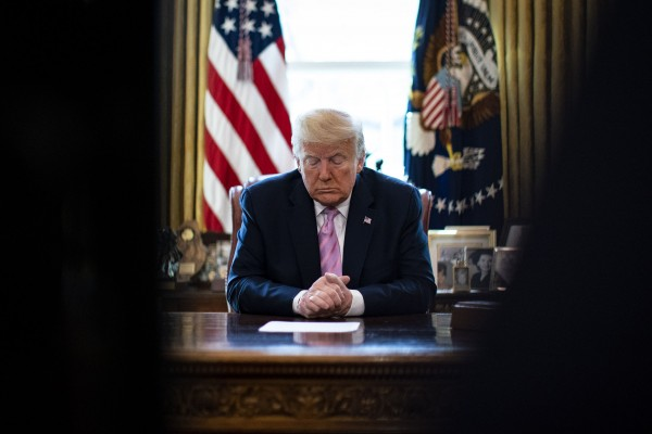 President Donald Trump bows his head during a Easter blessing by Bishop Harry Jackson, senior pastor at Hope Christian Church in Beltsville, Md., in the Oval Office of the White House on Friday, April 10, 2020 in Washington.