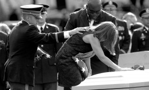 Dr. Susan Myers places a rose on the casket of her husband, Major General Harold J. Greene of the U.S. Army as her son, 1st Lt. Matthew Greene consoles her during Greene's burial at Arlington National Cemetery in Arlington, Va. on Thursday, August 14, 2014.