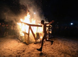 A shirtless Duke fan runs around a bonfire following Duke's 92-90 overtime win over North Carolina on February 20, 2015.