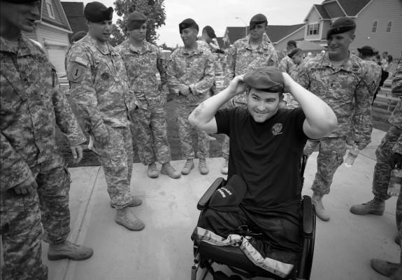 "Cpl. Cody Stanton is all smiles as he puts on his old beret outside of his new house in Holly Springs on Thursday, June 27, 2013. ""It found its way back home,"" said fellow soldier Lt. Jason Hollenbuch. Stanton received the new 5-bedroom house as a part of Operation: Coming Home V."