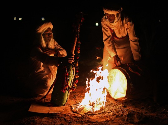 Camel herders hold their musical instruments near a fire to warm them up as the temperature in the Sahara Desert in Morocco begins to drop. The herders play traditional Moroccan Gnawa music, which a mystical form of music that was introduced by Sub-Saharan Africans.