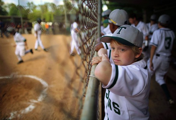 A young baseball player waits his turn to take the field as his fellow Trojan teammates take the field as they take on Woodlawn Middle School on Tuesday, May 20, 2014.  The Turrentine Trojans won 5-2.