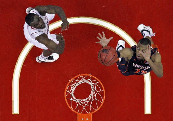 Virginia Cavaliers forward Akil Mitchell (25) makes a layup over North Carolina State Wolfpack guard Desmond Lee (5) as NC State takes on Virginia on Saturday, January 11, 2014 at the PNC Arena in Raleigh, N.C. Virginia won 76-45.