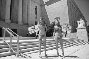 """PETA's """"Lettuce Ladies""""  Melissa Lacher, left, and Ashley Rhodes advertise for Capitol staffers and visitors to visit PETA's veggie dog stand outside the Rayburn House Office Building on Thursday, July 23, 2015. PETA holds the event annually to raise awareness of meet free diets."""