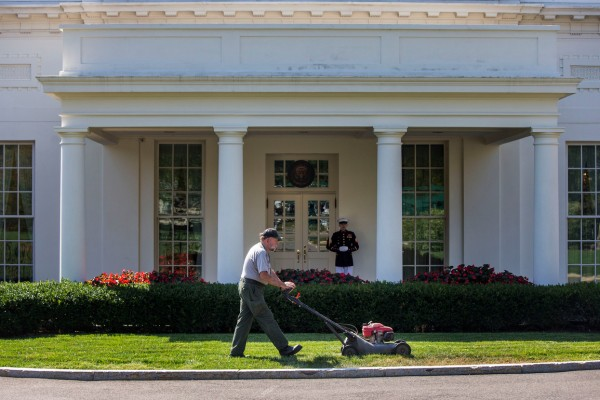 A National Parks Service worker mows the grass outside of the West Wing as a Marine stands at guard outside of the Oval Office at the White House, Friday, Sept. 16, 2016.