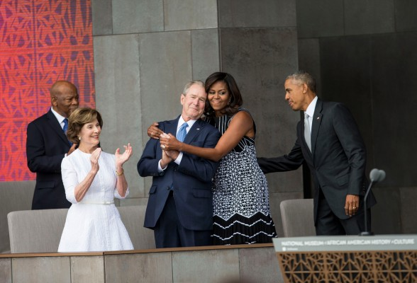 First Lady Michelle Obama hugs former President George W. Bush as President Barack Obama and former First Lady Laura Bush arrive at the Smithsonian National Museum of African American History and Culture opening ceremony, Saturday, Sept. 24, 2016.