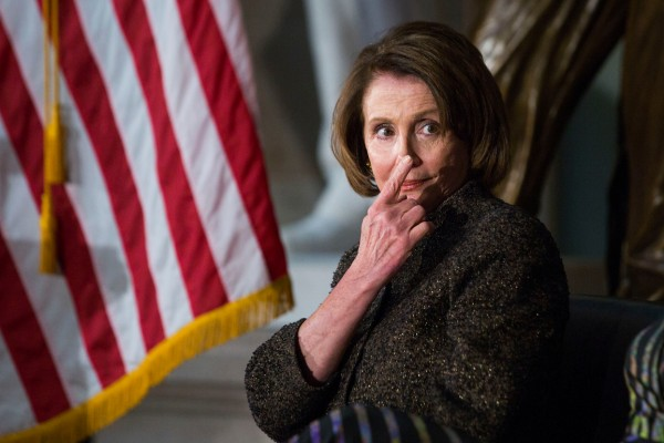 House Minority Leader Nancy Pelosi (D-Calif.) signals a member of her staff for her notes during a presentation to honor women veterans for their service, in Statuary Hall on Capitol Hill, Wednesday, March 2, 2016.