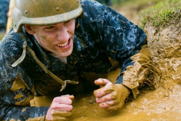 A plebe crawls through the mud under barbed wire during Sea Trials, a day of physical and mental challenges that caps off the freshman year at the U.S. Naval Academy in Annapolis, Md., on Tuesday, May 17, 2016.