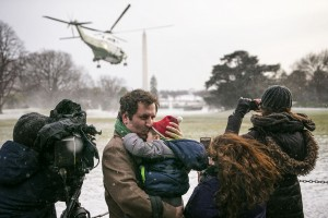 Reporters and guests cover as snow blankets the South Lawn of the White House as Marine One, carrying President Barack Obama, takes off on a snowy Saturday, January 7, 2016 in Washington.