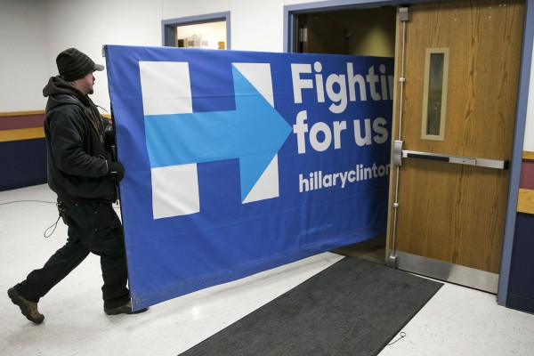 Workers carry out a campaign sign for democratic presidential candidate Hillary Rodham Clinton, after a campaign event in Marshalltown, Iowa, on Friday, Jan. 15, 2016.