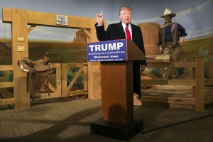 A wax statue of John Wayne watches as Republican presidential candidate Donald Trump speaks during a news conference at the John Wayne Museum, Tuesday, Jan. 19, 2016, in Winterset, Iowa.