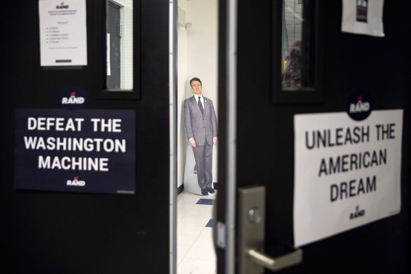 A cardboard cutout of republican presidential candidate Sen. Rand Paul, R-Ky., stands is seen through closing doors at his state campaign headquarters in Des Moines, Iowa, on Sunday, Jan 17, 2016.