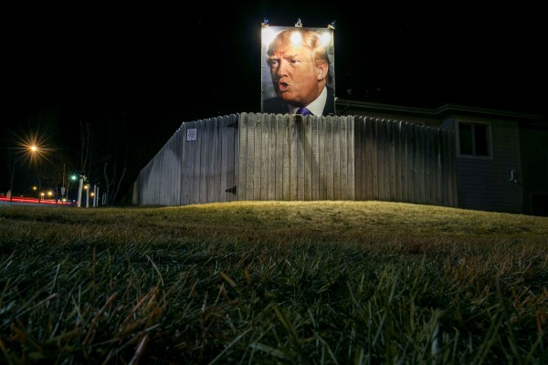 A giant poster of Republican presidential candidate Donald Trump stands on display in supporter George Davey's backyard in West Des Moines, Iowa, Wednesday, Jan. 27, 2016.