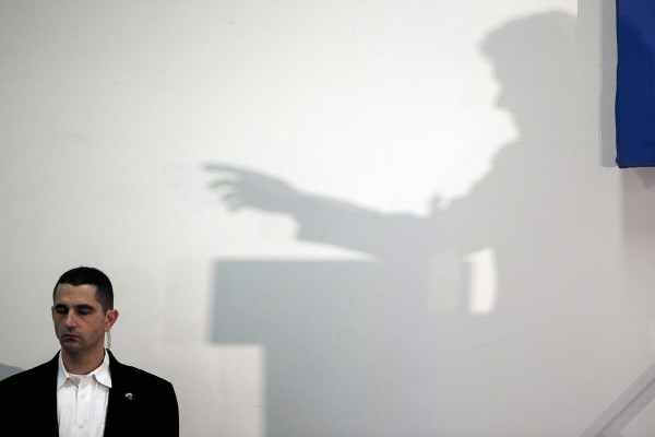 The shadow of former President Bill Clinton is seen next to a Secret Service agent as he speaks at a campaign event as he helps promote his wife, democratic presidential candidate Hillary Rodham Clinton, in Marshalltown, Iowa, on Friday, Jan. 15, 2016.