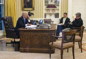 President Donald Trump speaks on the phone with Australian Prime Minister Malcolm Turnbull, in the Oval Office with National Security Advisor Michael Flynn and Counselor to the President Steve Bannon, Saturday, Jan. 28, 2017, at the White House in Washington. President Trump spoke on the phone with several world leaders, including Russian President Vladimir Putin and German Chancellor Angela Merkel.