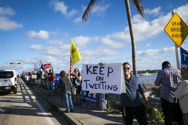 Supporters cheer as President Donald Trump's motorcade returns to his Mar-a-Lago club after spending the morning at Trump International Golf Club, in West Palm Beach, Fla., Dec. 31, 2017.