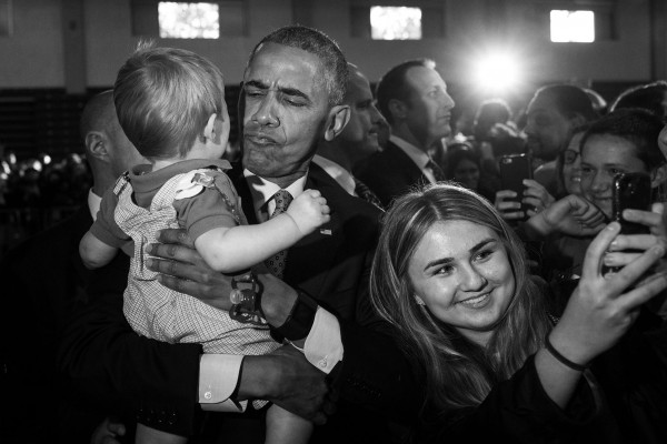 President Barack Obama tries to cheer up 10-month-old Brooks Breitwieser as Molly Matscik, 17, from Worthington, Ohio, takes a selfie before a campaign event for Democratic presidential candidate Hillary Clinton at Capital University, Tuesday, Nov. 1, 2016, in Columbus, Ohio.