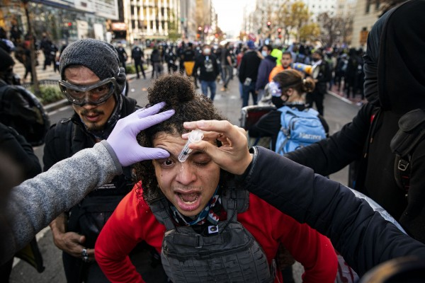 A demonstrator that is against U.S. President Donald Trump has his eye washed off following a chemical being sprayed in the air, as demonstrators march in support of President Donald Trump and in protest the outcome of the 2020 presidential election Black Lives Plaza, on December 12, 2020 in Washington, DC. Thousands of protesters who refuse to accept that President-elect Joe Biden won the election are rallying ahead of the electoral college vote to make Trump's 306-to-232 loss official.